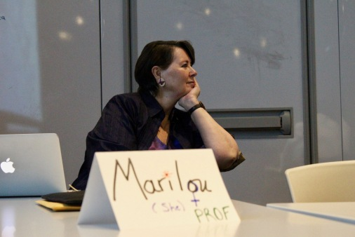 "Senator McPhedran listens to lecture. In front of her is a sign that reads "" Marilou (She) + Prof"""