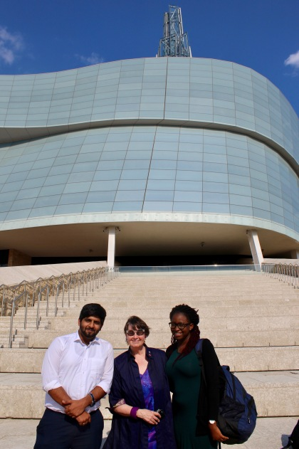 two students pose wtih Senator McPhedran on steps outside CMHR