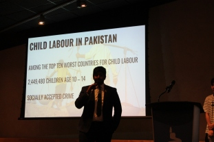"Student presents for group project. Slide in background is titled ""Child Labour in Pakistan"""