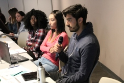 Student asks question while two students look on