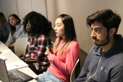 2018 Student engages in class while speaking into mic while two students look on.