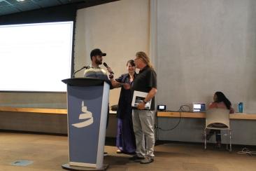student thanks Dr. Kornelsen for presentation while Senator McPhedran looks on