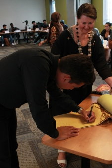 Guest Instructor Jorge Requena Ramos signs the Global College Registrar held by Senator McPhedran