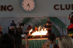 Afro-Caribbean Pavilion dancer does limbo under pole on fire