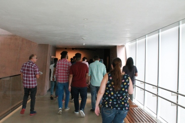 Students are photographed from behind walking though CMHR hallway