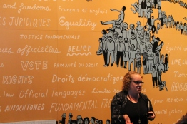 Amber Parker, CMHR Interpreter, standing in front of an outline of Canada in the Protecting Rights in Canada gallery