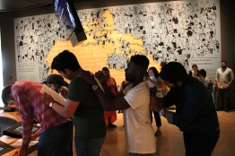four students use each others backs to fill in form at CMHR