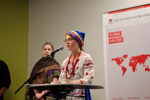 2018 Student stands at podium in traditional Ukrainian dress for their group presentation.