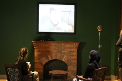 Two students sit in chairs and watch TV as part of display in Mandela: Struggle for Freedom