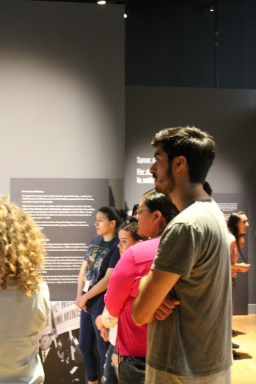 four students in a line listening to Isabelle Masson in the Mandela: Struggle for Freedom exhibit