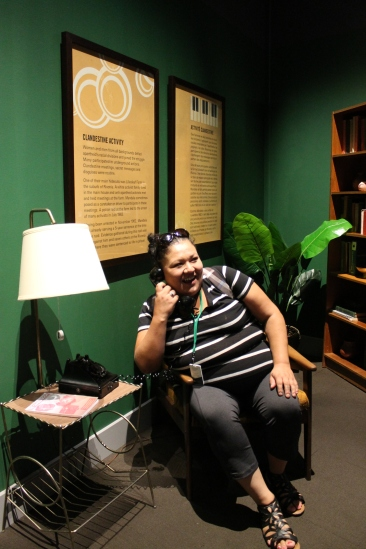 student sits in chair on phone as part of the Mandela: Struggle for Freedom exhibit
