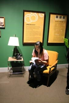 student sits in chair reading a book as part of the Mandela: Struggle for Freedom exhibit