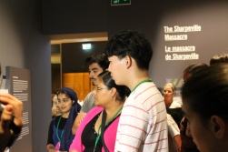 five students stand in line listening to Isabelle Masson in the Mandela: Struggle for Freedom exhibit