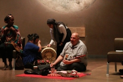 Albert McLeod explains pipe ceremony while one student offers smudge to another student preparing to drum and sing for the ceremony